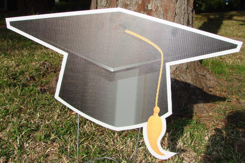 yard sign of graduation cap