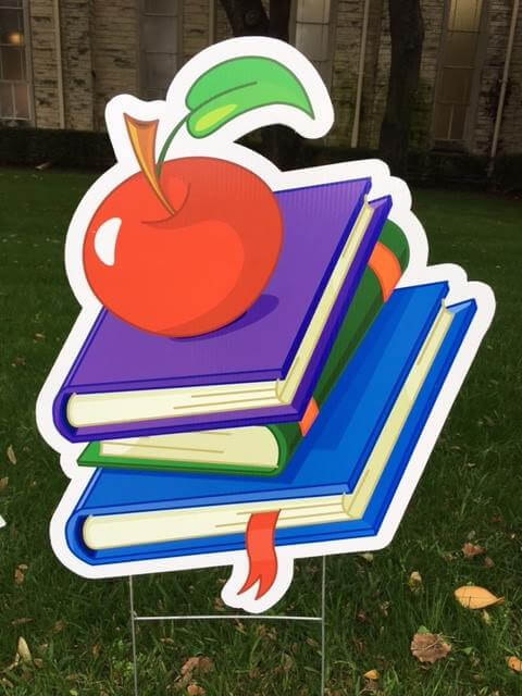 yard sign of school books and apple