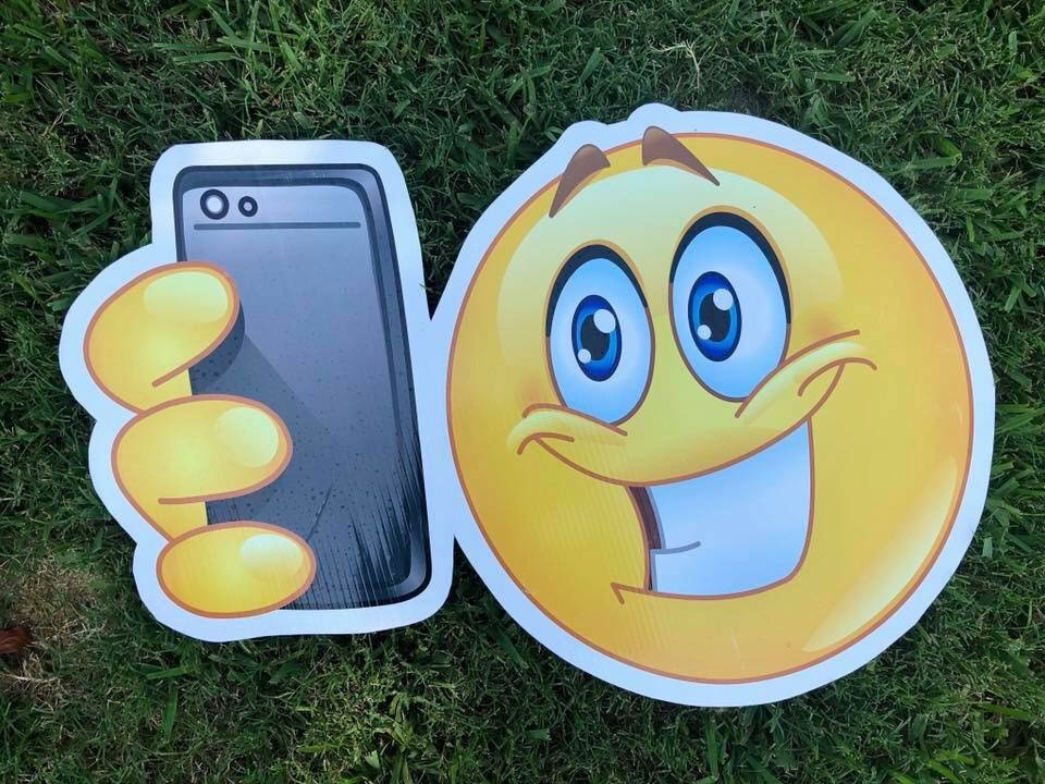 lawn graphic of looking at phone emoji