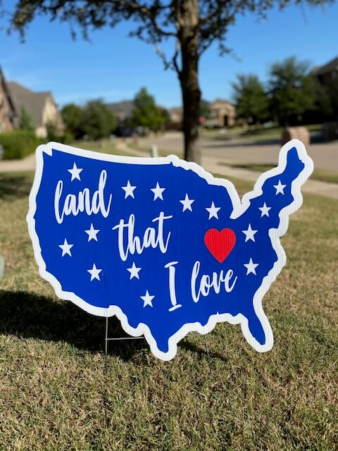 "A silhouette of the US with the words ""land that I love"""
