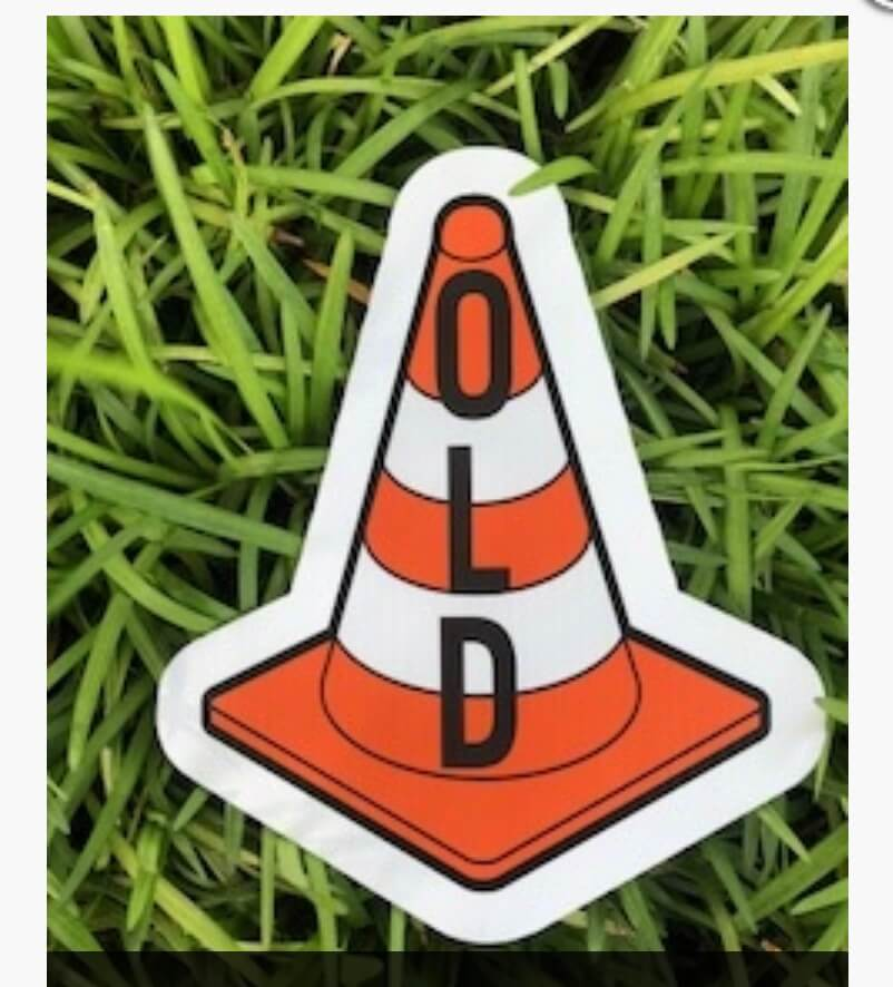 "A street cone with the word ""OLD"" on it"