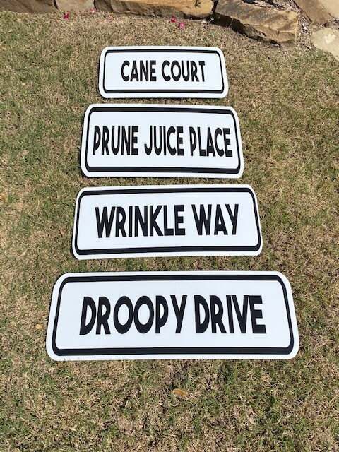 "Street signs reading ""Cane Court"", ""Prune Juice Place"", ""Wrinkle Way"" and ""Droopy Drive"""