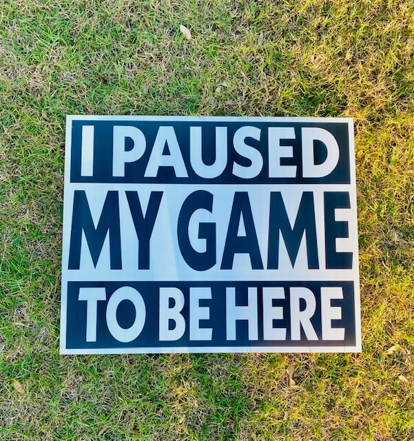 "A sign that reads ""I paused my game to be here"""