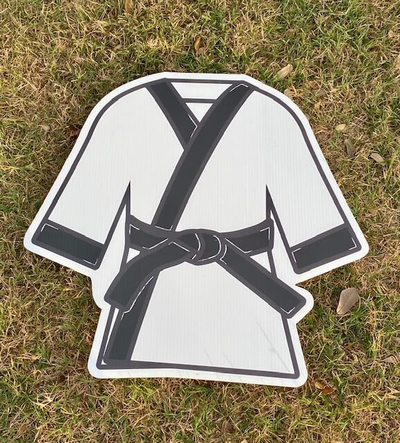 A white karategi with a black belt