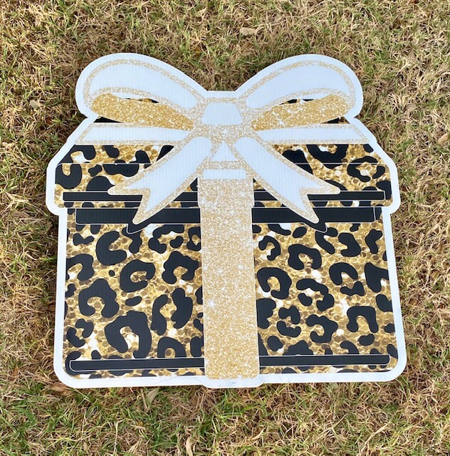 A gold leopard print gift box with a sparkly gold bow
