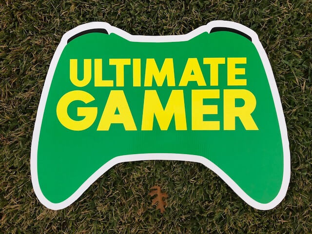"a sign in the shape of an xbox controller that says ""Ultimate Gamer"""