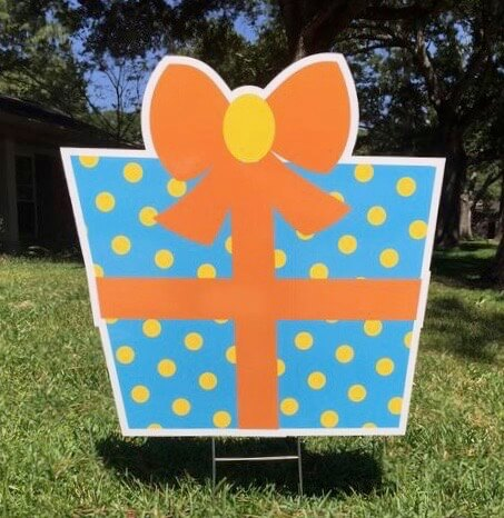 A blue gift box with yellow polka dots and an orange bow