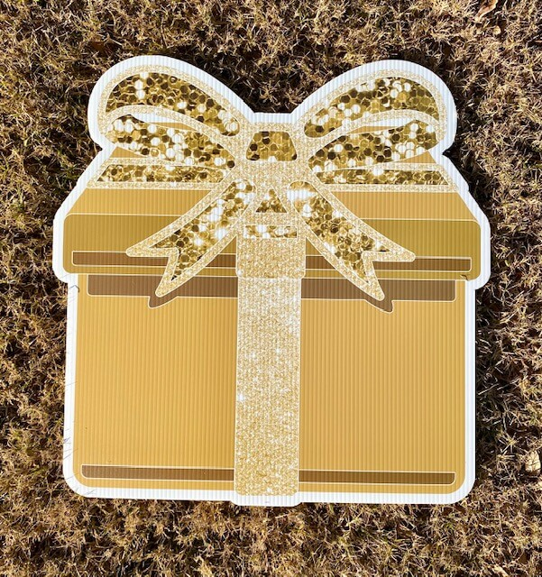 A gold giftbox with a sparkly gold bow