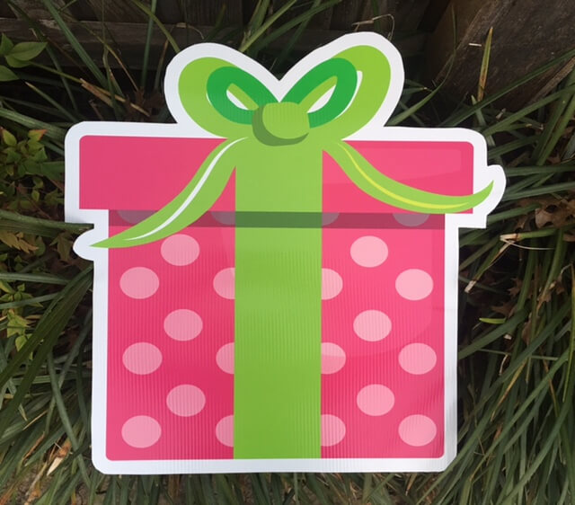 A pink polka dot gift box with a green bow