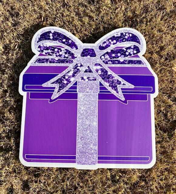 A purple gift box with a sparkly purple bow