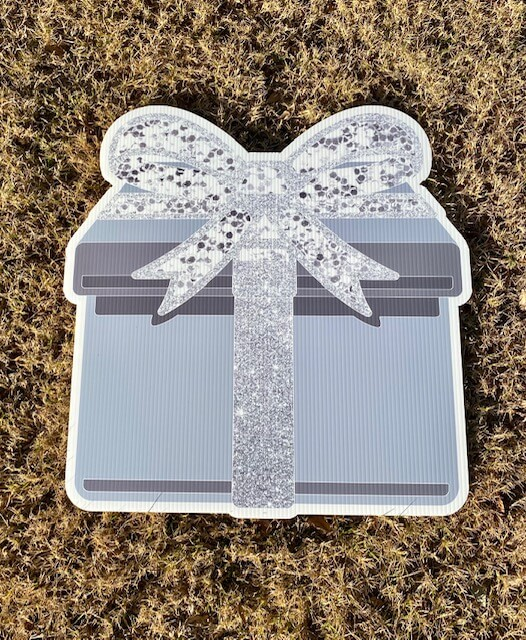 A silver gift box with a sparkly silver bow