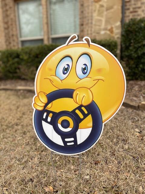 Smiling emoji with a steering wheel
