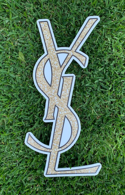 Gold sparkly Yves Saint Laurent logo