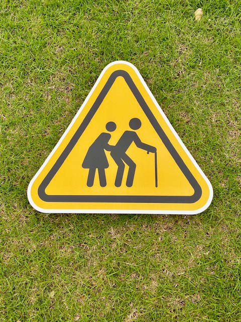 Yellow road sign of elderly couple crossing